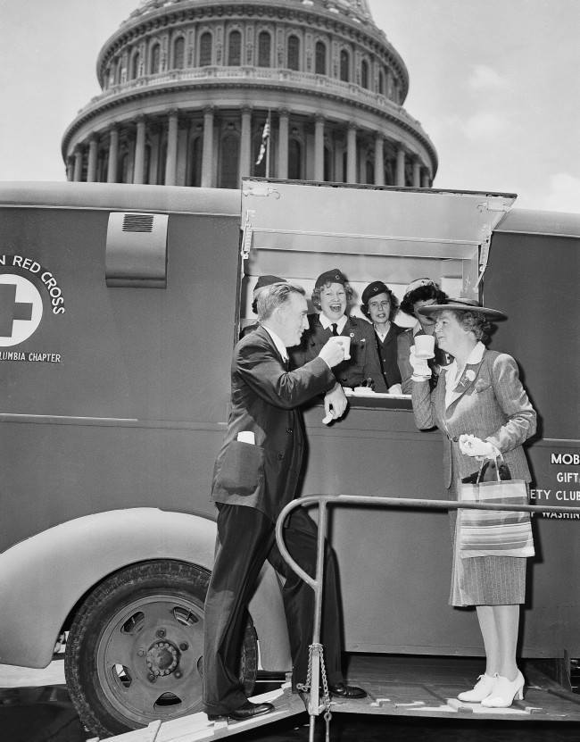 Red Cross workers, demonstrating one of the five mobile canteen units acquired for relief work in the event Washington has an air raid, stop by the Capitol on June 18, 1942, and dish up mugs of coffee for Senator Joseph C. O'Mahoney, left, (D-Wyo.) and Rep. Edith Nourse Rogers, right, (R-Mass.). (AP Photo/Robert Clover)