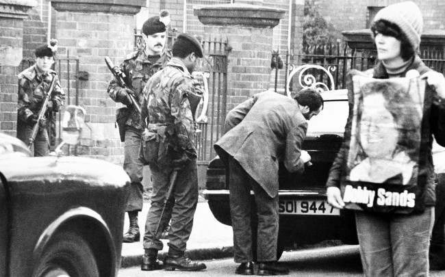 A protestor supporting the IRA hunger strikers stands in the center of the Catholic Falls road in Belfast on Friday, May 1, 1981, as troops of the royal fusiliers check cars at a roadblock. Tension remained high in Belfast, in anticipation of the death of IRA hunger striker Bobby Sands. (AP Photo/Peter Kemp)