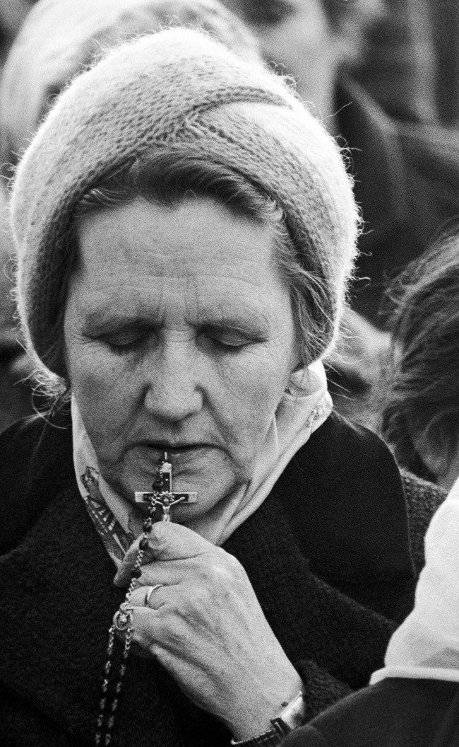 An unidentified woman holds her rosary to her lips, during a prayer service for Bobby Sands and his fellow IRA hunger strikers, in a Catholic area of Belfast on Friday, May 1, 1981. Sands is now in the 62nd day of his hunger strike at Northern Ireland's Maze prison. (AP Photo/David Caulkin) Ref #: PA.11670696  Date: 26/04/1981