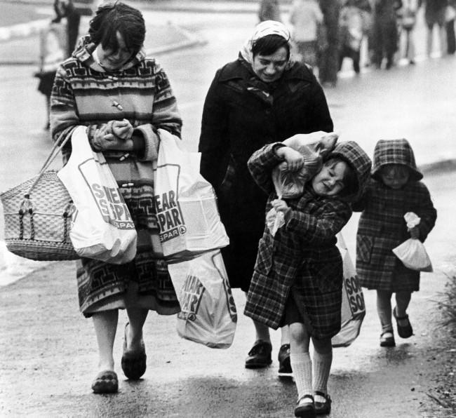 An unidentified Catholic family struggles home, loaded down with provisions, after a shopping expedition in Belfast on Thursday, April 30, 1981. Homes in Belfast have been collecting supplies recently in case of major civil disorders following the expected death of IRA hunger striker Bobby Sands. (AP Photo/Peter Kemp)