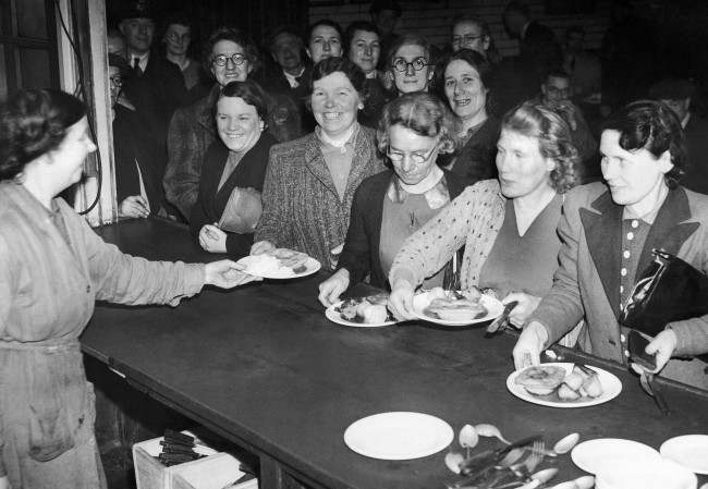 Nearly half of the post office staff consists of women now that the men are being absorbed into the forces. In their own training school they learn everything connected with the collection and delivery of the mail. A meal from the canteen forms a welcome lunch-time break after concentrated studies on Feb. 16, 1942.