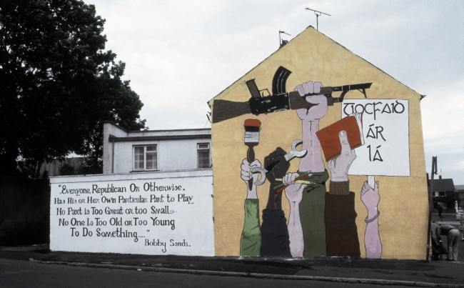 "A mural painted on the side of a house in Londonderry shows a Catholic's perspective of the tension in Northern Ireland in 1984. The poem by the late hunger striker Bobby Sands written next to the painting states that ""no one is too old or young to do something."" (AP Photo/Peter Kemp) Ref #: PA.11809603  Date: 01/01/1984"