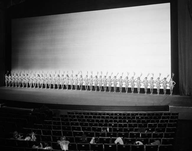 "To accent the size of the giant 70-foot-wide new screen at Radio City Music Hall in New York, the Rockettes, all 36 of them, stretch across the stage, 72 feet wide, shownJan. 8, 1954. The screen was installed for the theater's first Cinemascope film, ""Knights of the Round Table"". It will remain as part of the permanent equipment. Thirty-three feet high, the Magnaglo-Astrolite screen shows an image 70 feet wide and 28 feet high. It is believed to be the world's largest movie screen. It is made of four laminated layers of cloth, plastic, and silver. ("