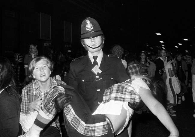 A policeman carries a young female fan outside the New Victoria Theatre in London. PA/PA Archive/Press Association Images