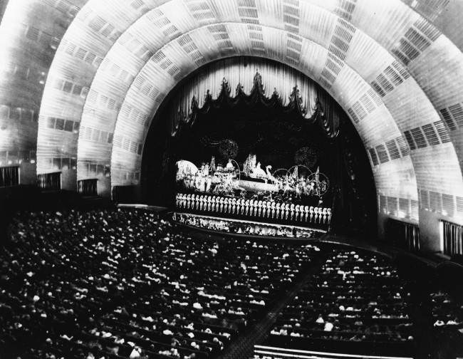 The unique, art deco auditorium of Rockefeller Center's Radio City Music Hall, the world's largest theater with a 60-foot high proscenium arch, and a full city block in width, is seen in 1968. The Radio City Music Hall Symphony Orchestra can be seen in the pit. The theater seats 6,200 people. (AP Photo) Date: 01/01/1968