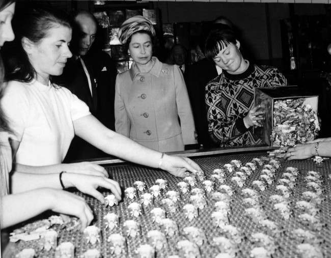 "*Scanned low-res from print, high-res available on request* Queen Elizabeth II watches as miniature models are spread on a conveyor belt during her visit to the makers of the ""Matchbox"" models series - Lesney Products and Company Ltd - at Hackney Wick, London. Ref #: PA.13433485  Date: 12/11/1969"