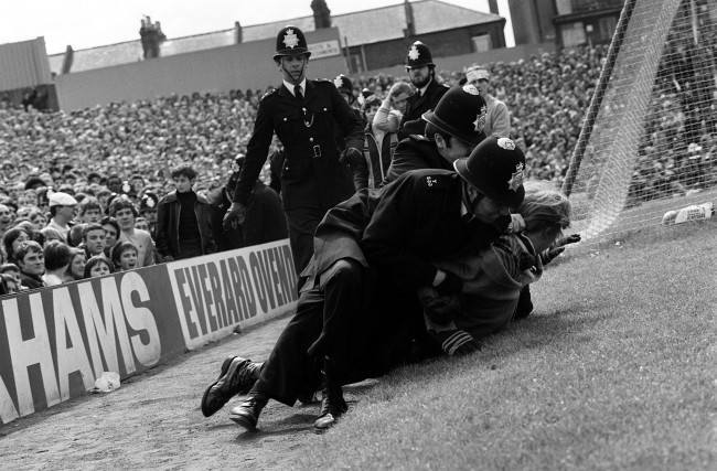 Hooligans Arsenal v Villa Police wrestle a spectator to the ground after fighting broke out at Highbury during the match between Arsenal and Aston Villa. Date: 02/05/1981