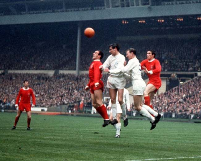 Liverpool players Ian St John (left, red shirt) and Ron Yeats (right), battle for the ball with Leeds United players Norman Hunter (2nd left, white shirt) and Jack Charlton (2nd right),