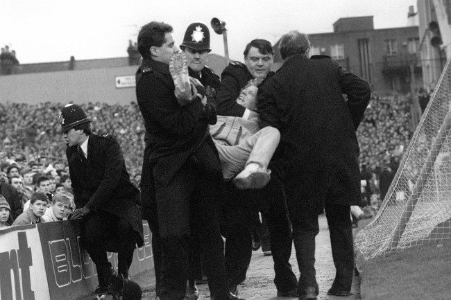 ccer - FA Cup - Third Round - Arsenal v Millwall - Highbury Police handle a fan who has been pulled out of the crowd at the start of the match. Date: 09/01/1988
