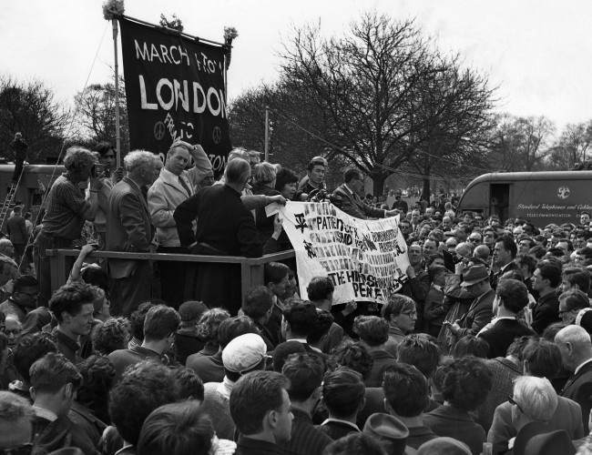 Two survivors of the Hiroshima atomic bomb hold up a banner as they join leaders of the Easter Ban-the-Bomb march on the dais in Londonís Hyde Park on April 23, 1962, at the mass rally climaxing the 50-mile march from Aldermaston. They are Miyoko Matsubara, a 29-year-old nurse, and Hirosama Hanabusa, 18, a law student. In black at near end of dais is Canon John Collins of St. Paulís Cathedral, chairman of the campaign for nuclear disarmament.