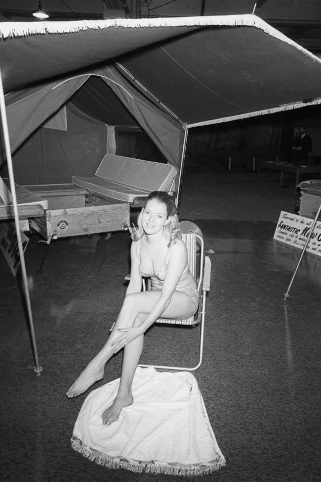 Wendy Pattenden, 26, of Bournemouth, demonstrates a tent trailer at Colex ' 70, the 12th annual Camping and Outdoor Life and Travel Exhibition which opened at Olympia, London. The trailer is made by Concraft Trailers of Roundhill, Tusmore in Bicester, Oxfordshire. Archive-pa143437-1 Ref #: PA.16531914 Date: 31/12/1969