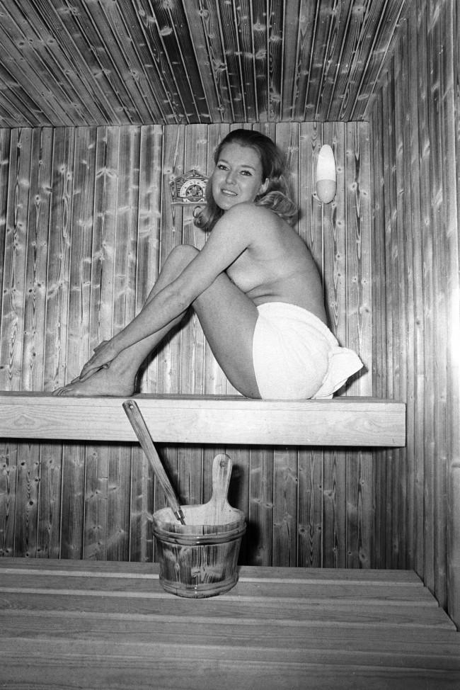 In London's icy weather, Wendy Pattenden, 26, of Bournemouth, discarded her clothes to demonstrate a sauna for campers at Colex '70, the 12th annual Camping and Outdoor Life and Travel Exhibition which opened at Olympia, London. The sauna is from Norpe Saunas of Finland. Archive-pa143437-1 Ref #: PA.16532025 Date: 31/12/1969