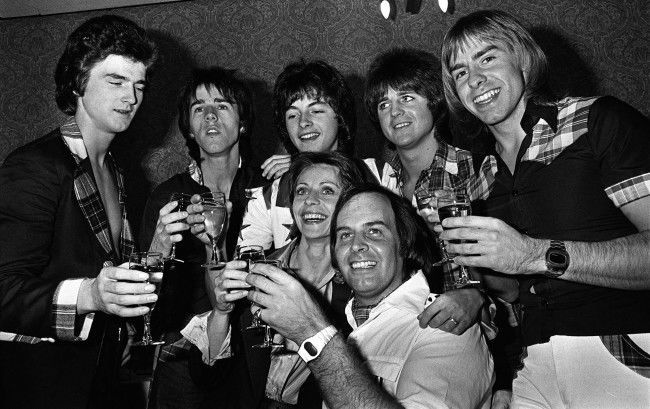 The Bay City Rollers, currently on a concert tour of Britain, celebrate with champagne at a Manchester hotel after the announcement that their 36-year-old manager, Tam Paton (centre) has become engaged to Czech-born 28-year-old London art student Marcella Knaiflova. PA/PA Archive/Press Association Images