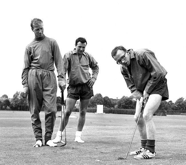 Nobby Stiles, the Manchester United wing-half, concentrates hard during a putting session at the Bank of England Sports Club ground, Roehampton, London, where he was training with other members of England's World Cup squad. Watching him are Leeds United half-back Jackie Charlton (left) and Blackpool full-back Jimmy Armfield.