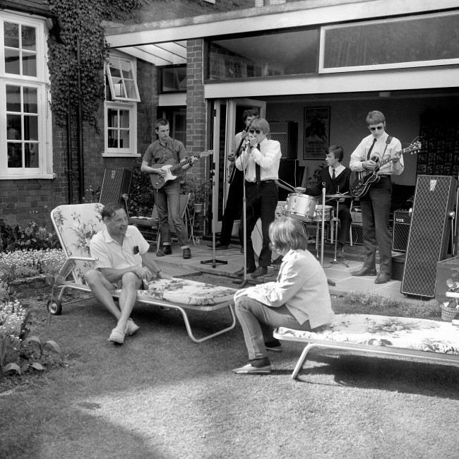 Lord Willis, who recently attacked 'The Beatle Cult' in a House of Lords speech is pictured with his daughter Sally, as they listen to the Yardbirds in the back garden of his home in Shepherd's Green, Chislehurst, Kent. The Yardbirds, a pop-group of five ex-public school boys from the Richmond area of Surrey, had unexpectedly visited Lord Willis to explain 'what pop music is all about'. Lord Willis, the scriptwriter who created television's 'Dixon of Dock Green' invited them into the garden where he was sunning himself. After a discussion, he then asked them to play. The group, who favour hairstyles short and long, are left to right: Eric Clapton, 19, Paul Samwell Smith, 21, Keith Relf, 21, Jim McCarty, 20 and Christopher Dreja, 18.