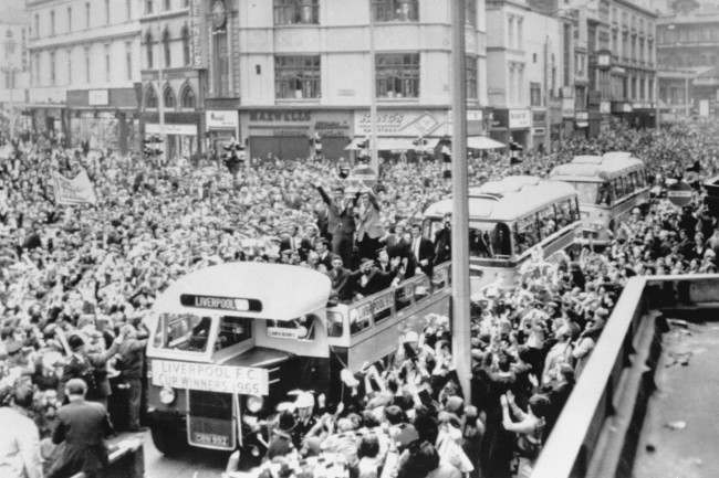 Displaying the FA Cup to the wildly cheering crowds, the Liverpool FC players are seen on their triumphal drive in an open top coach to the Town Hall from Lime Street Station for a civic reception on their return to Liverpool after beating Leeds Utd in the Cup Final at Wembley. Crowds estimated between 200,000 and 250,000 gave them a tumultuous welcome. The excited fans burst through the barriers and there were hundreds of casualties.