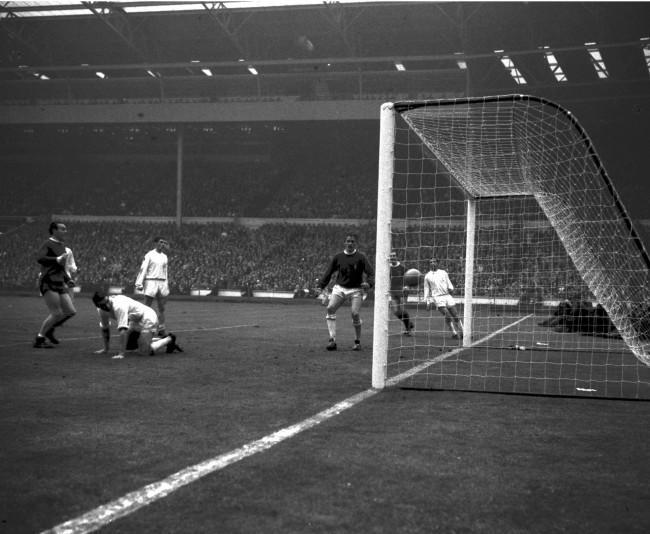 Leeds goalkeeper Sprake watches, helpless, as the ball shoots into the net to notch Liverpool's first goal, in the FA Cup Final at Wembley. Looking on is Liverpool centre forward Ian St. John (left). Others are left to right, Bell and Hunter of Leeds, Byrne (Liverpool) and Reaney (Leeds). Liverpool won 2-1, all the goals being scored in extra time.