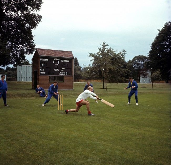 England's Bobby Charlton (white shirt) wafts his bat at the ball, watched by (l-r) Terry Paine, Bobby Moore, Martin Peters, Gerry Byrne and Peter Bonetti, as the England squad relax with a game of cricket during a training session at Roehampton Ref #: PA.2219404  Date: 15/07/1966