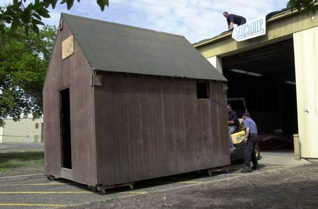 Workers move the cabin that Unabomber Theodore Kaczynski lived in, out of a storage facility in Rancho Cordova, Calif., Thursday, May 1,2003. The cabin was to be dismantled and moved to another location, but a last minute change of plans stopped the razing. The cabin, built by Kaczynski in Monatana, was trucked to Rancho Cordova, a suburb of Sacramento, in December of 1997 by the federal defenders office. The cabin was stored by a company that specializes in the secure storage of critical evidence and sensitive material. (AP Photo/Rich Pedroncelli) Ref #: PA.2825961  Date: 01/05/2003