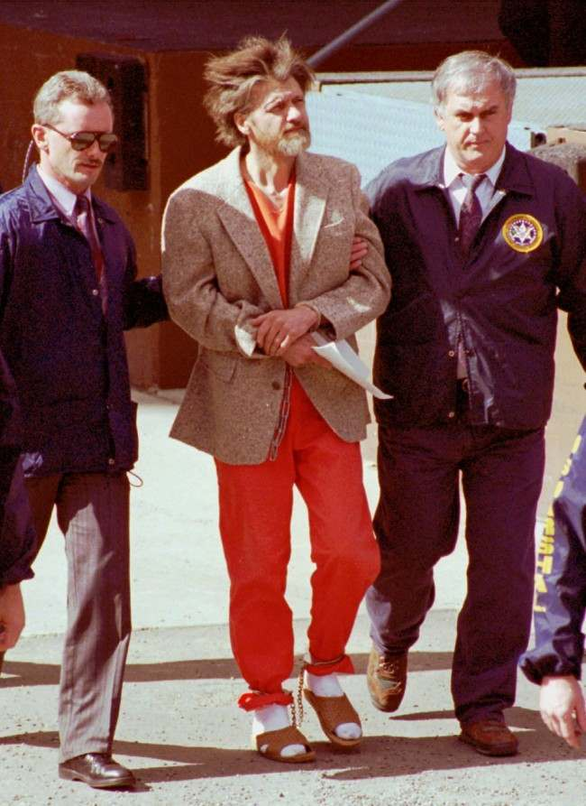 Wearing a sport coat over his jail coveralls, Theodore John Kaczynski is escorted in handcuffs and ankle shackles by two unidentified federal agents as they leave the federal courthouse in Helena, Mont., Thursday, April 4, 1996. Federal agents found a partially assembled bomb in the mountain shack of the former Berkeley math professor suspected of being the Unabomber.