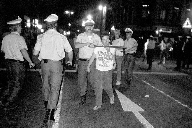 Soccer - European Championships 1988 - West Germany An England fan is led away by a policeman holding a baton to this throat Date: 18/06/1988