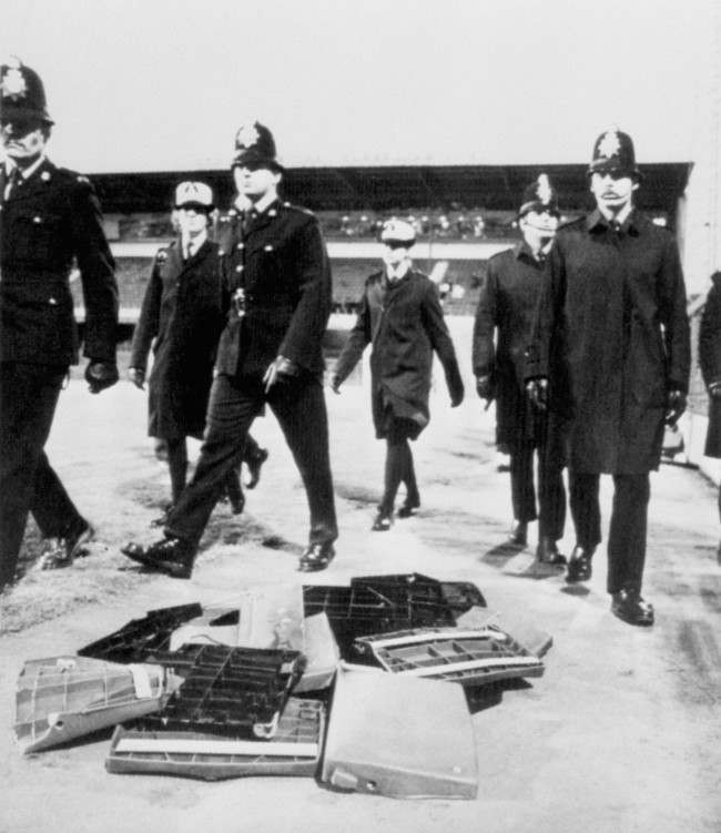 Soccer - FA Cup - Fourth Round - Derby County v Chelsea - Baseball Ground Police officers skirt around a pile of seats thrown from the stands by irate Chelsea fans as they move towards the away end to quell the violence that erupted when Derby County scored their winning goal Date: 29/01/1983