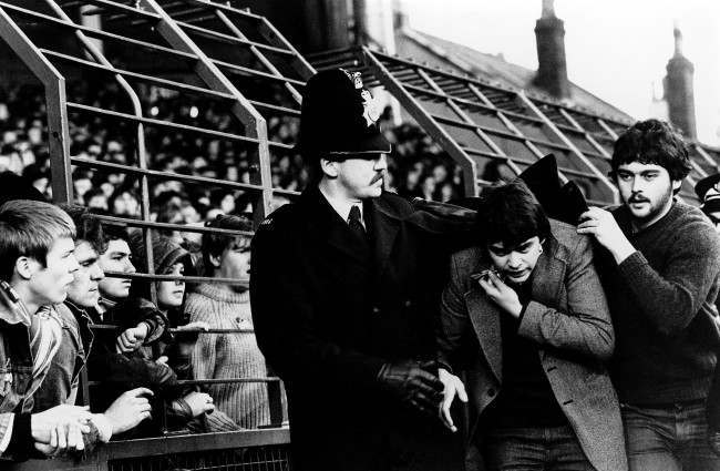 Soccer - Football League Division One - Liverpool v Tottenham Hotspur A Tottenham fan is escorted past the Anfield Road end by police after having a dart thrown at him by hooligans  Date: 06/12/1980