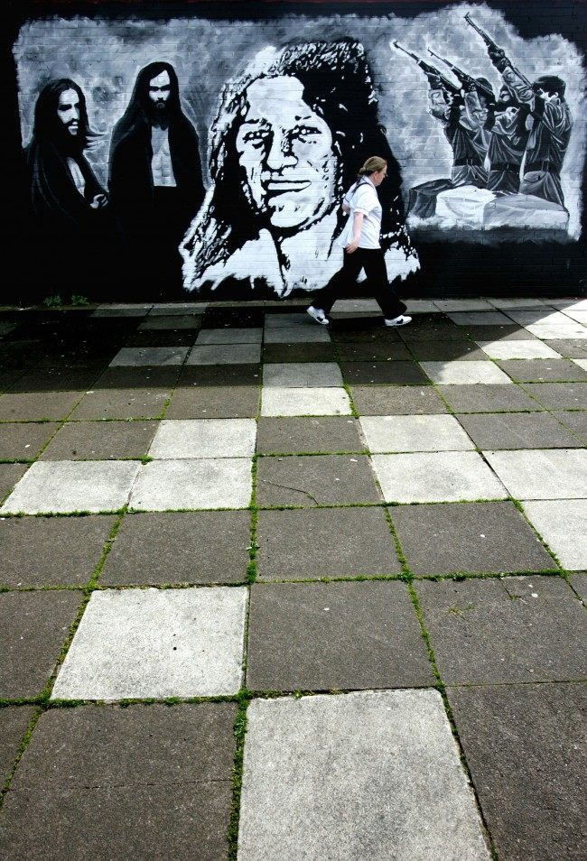 A woman passes a wall mural depicting Bobby Sands, at centre, commemorating the IRA hunger stikers in West Belfast, Northern Ireland, Friday, May, 5, 2006.