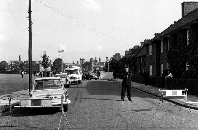 Screens surround the crime scene and a policeman stands guard. The officers, cruising in a police car were shot when they stopped to question men in another car. In the background is Wormwood Scrubs prison. Ref #: PA.3565278  Date: 13/08/1966