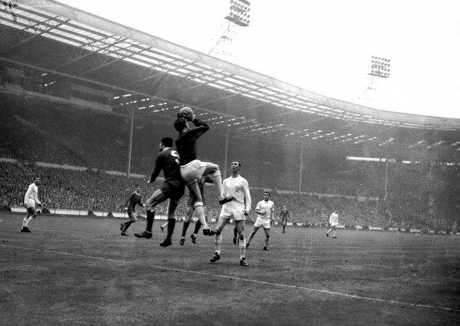 Leeds United goalkeeper Gary Sprake (c) claims a cross under pressure from Liverpool's Ian St John (l), watched by teammate Jack Charlton (r)
