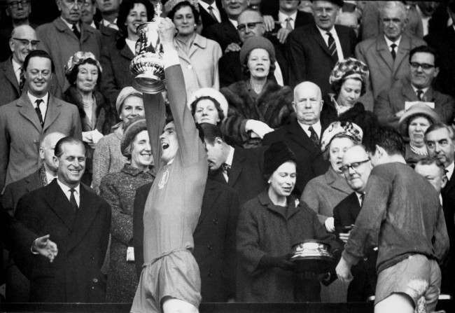 Liverpool captain Ron Yeats (second l) lifts the FA Cup as teammate Tommy Lawrence (r) collects the base of the trophy from HM Queen Elizabeth II (second r)