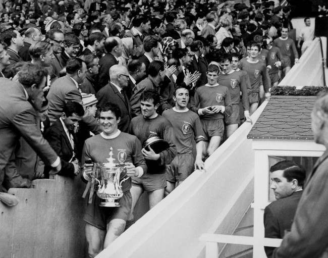 Liverpool captain Ron Yeats (l) carries the FA Cup down Wembley's 39 steps, followed by teammates Tommy Lawrence (carrying base of cup), Peter Thompson, Geoff Strong, Tommy Smith, Ian Callaghan, Wilf Stevenson, Chris Lawler, Roger Hunt, Ian St John and Gerry Byrne