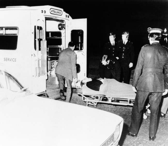 A wounded man is carried into the waiting ambulance on March 20, 1974 in London in the mall the approach road to Buckingham Palace after shots had been fired at Princess Anne and her husband, Mark Phillips, as they drove in their Rolls Royce toward the palace. Also involved in the shooting was a London taxi which was following the Royal Car at the time. Princess Anne's bodyguard, her chauffer and a man in the taxi were hit by the gunmen. The Princess and husband escaped unharmed. (AP Photo) Ref #: PA.7090585  Date: 20/03/1974