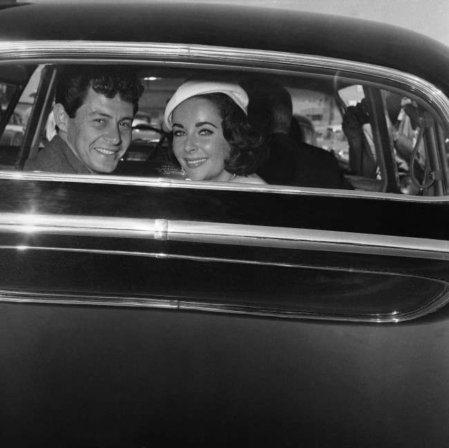 Liz Taylor and Eddie Fisher flash happy smiles through the window of their auto on May 12, 1959 in Las Vegas, as they were driven off from the county courthouse where Fisher first divorced Debbie Reynolds and then obtained a license to marry Miss Taylor. The wedding was to take place a couple of hours later in a Jewish synagogue. (AP Photo) Ref #: PA.7334972