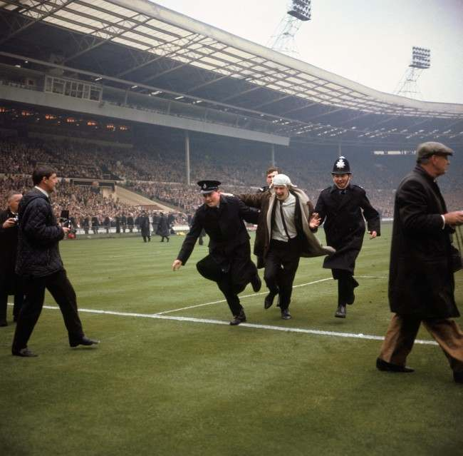 A jubilant Liverpool fan is escorted off the pitch by policemen after running on to celebrate his team's winning goal