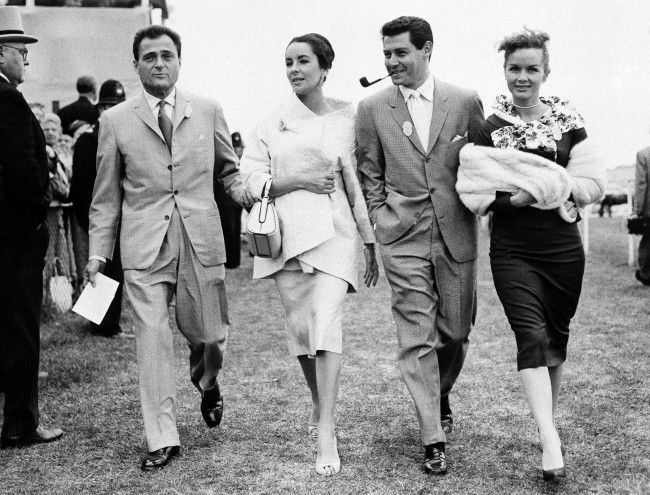 A quartette of film folk stroll along the turf on Epsom Downs, on June 5, 1957 during the 178th Derby Stakes in England. Left to right, Mike Todd and his wife Elizabeth Taylor, singer Eddie Fisher, and his wife actress Debbie Reynolds. (AP Photo) Ref #: PA.7566521 Date: 05/06/1957