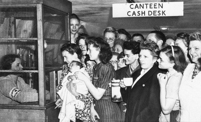 Deep in tubes underneath underground railway lines in London shelters provide safety from buzz bombs, July 25, 1944. They crowd around the canteen cash desk to get receipts for money spent in the canteen on refreshments