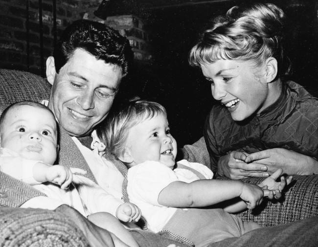 Singer Eddie Fisher, out of the hospital in time for Father's Day, cuddles his two youngsters four-month old Todd, left, and 19-month-old Carrie. Looking on is their equally famous mother, actress Debbie Reynolds. Eddie spent ten days in the hospital following an appendix flare-up. (AP Photo) Ref #: PA.8554988  Date: 14/06/1958