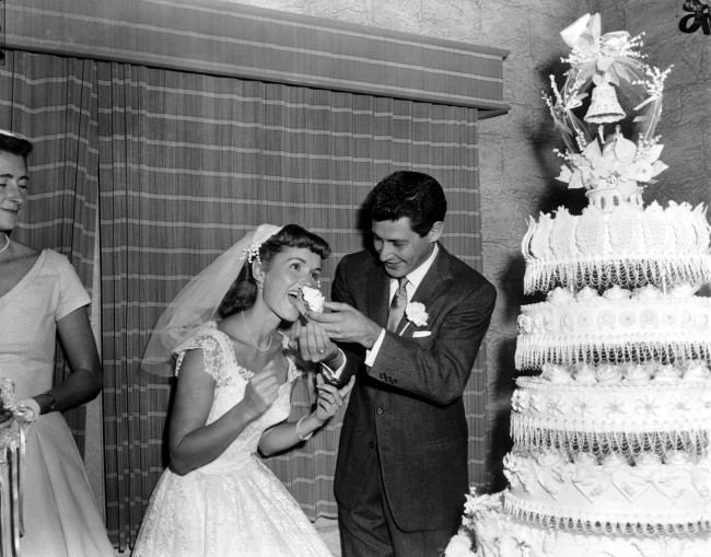Singer Eddie Fisher, 26, feeds a piece of wedding cake to his bride, actress Debbie Reynolds, 23, following their marriage at Grossinger, N.Y., on Sept. 26, 1955. (AP Photo/Marty Lederhandler) Ref #: PA.8692524 Date: 26/09/1955
