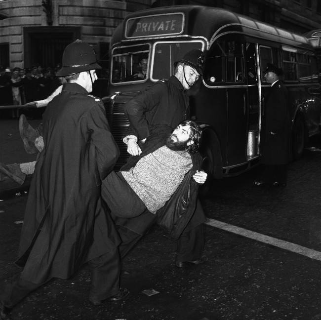 A long-haired young man, wearing a beard and beatnik style clothes, is carried to a waiting van by police after being arrested during the huge Ban-the-bomb rally in London's Trafalgar Square, United Kingdom on Sept. 17, 1961. Many arrests were made during skirmishes between police and demonstrators as the crowd grew to well over 10,000. Hundreds of extra police were called on duty to deal with the crowds.