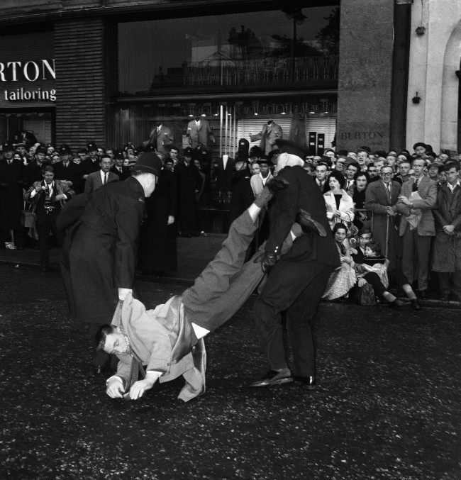 A well-dressed man is dragged away, head down, by police officers after sitting down during the huge Ban-the-bomb rally in London's rain-soaked Trafalgar Square, United Kingdom on Sept. 17, 1961. Note shouting woman in right background.
