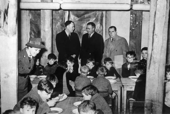 The delegates visit a canteen in a Brussels school in Belgium on Jan 28, 1941. From left to right are: Mr. G. Murray, Mr. Mac Donald, and Mr. Frederic Dorsey Stephens, Head of the delegation.