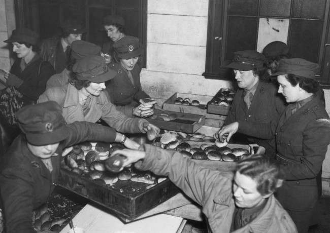A busy scene in the Legion's dockside hut headquarters in London, Feb. 27, 1943 as mobile canteen drivers and helpers load up trays of rolls for the midmorning lunch they serve to dock laborers.