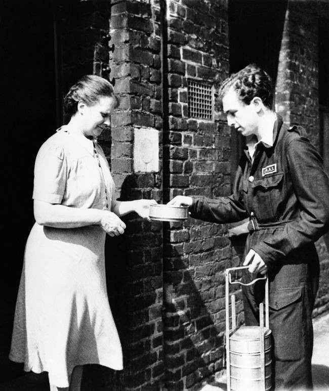 Christopher Ounsted, driver of the mobile canteen, delivering a hot dinner to a woman during his rounds in London on Sept. 17, 1941. The canteen, a gift from the U.S., would be idle normally, as a result of the lull in the blitz, but it is put to use to feed the poor, aged and homeless.