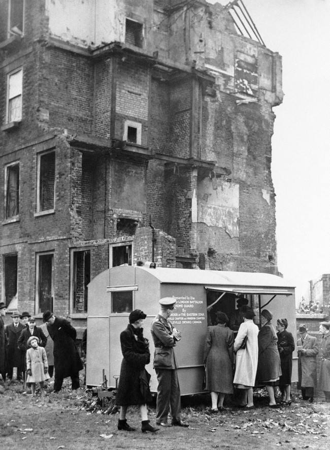 A canteen presented by the people of Canada to the London home guard is set up alongside a bomb-shattered building in London on Dec. 28, 1942. The canteen was presented at a ceremony on December 13 at which the High Commissioner for Canada, Vincent Massey, presided. (
