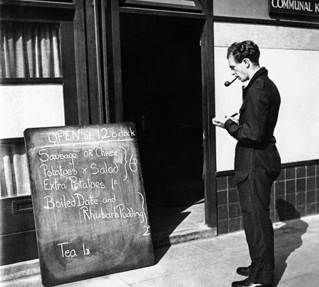 Christopher Ounsted, volunteer driver of the mobile canteen, stops at a communal kitchen to copy the day's menu prior to starting out on his day's rounds in London on Sept. 17, 1941. He presents a list of the food available to the people he visits, permitting them to make a selection.