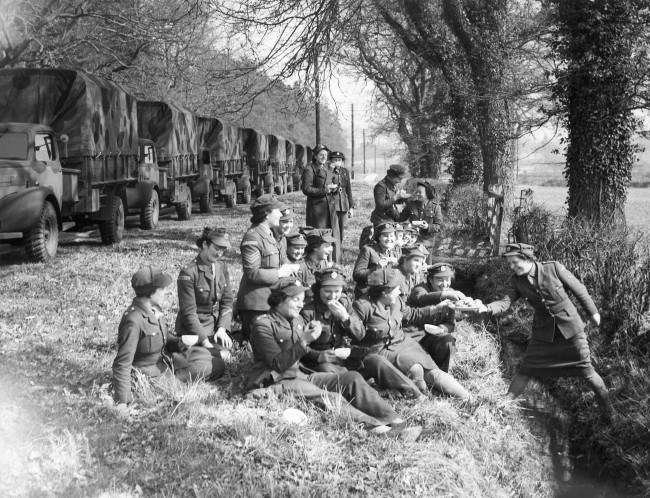 "A convoy of new lorries was driven entirely by A.T.S. personnel from a Bedfordshire factory to a Gloucestershire R.A.S.C. depot. Their 100 mile journey was broken by a '""pause for refreshmentÂ' at the mobile canteen sent from H.Q. to meet the convoy, March 25, 1942. A halt on the way during the passage of the convoy-and the A.T.S. girls enjoy an Al Fresco lunch at the roadside in a picturesque setting while their lorries are lined up behind."