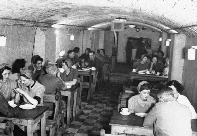 Lunchtime in the underground factory's canteen in England April 11, 1944. Most of the workers are women. The benches are pews from a nearby bombed out church.