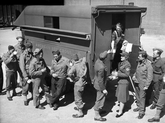 An American Red Cross mobile canteen on the quay of a Northern Ireland port furnishes hot coffee for some of the American soldiers who landed there with the largest A.E.F. of the current war, May 27, 1942. The uniformed Red Cross worker is Miss Louisa Farrand of New York City.