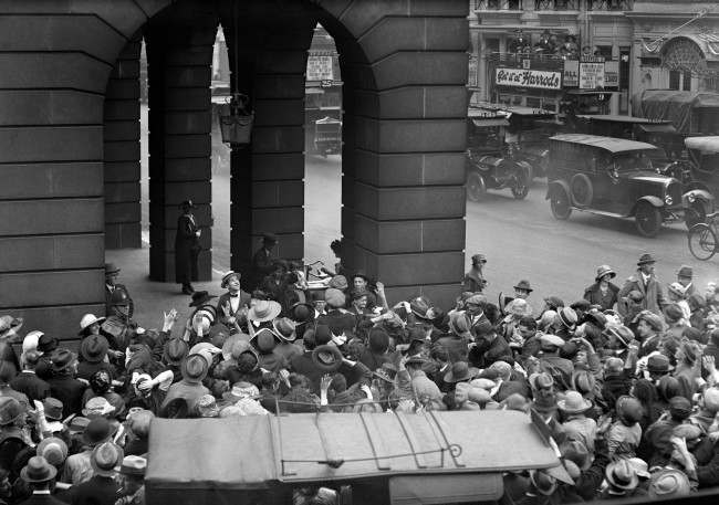 Charlie Chaplin throwing carnations to the crowd from his balcony at the Ritz Hotel after his arrival in London. PA/PA Archive/Press Association Images